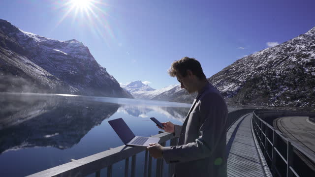 vídeos y material grabado en eventos de stock de man in a grey suit using a laptop and cell phone on dam near a lake and snowy mountains - toma ancha