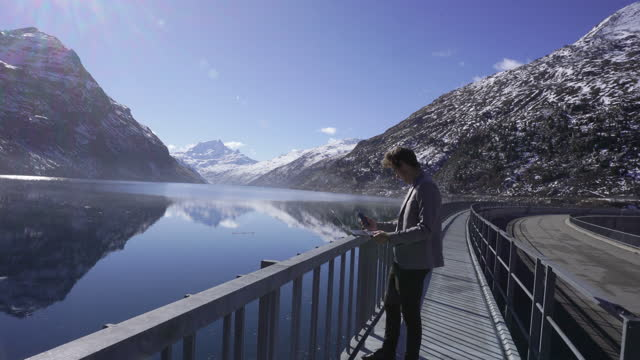 man in a grey suit using a laptop on dam near a lake and snowy mountains - standing stock videos & royalty-free footage