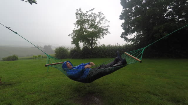 man in a hammock in the rain in the countryside - waterproof clothing stock videos and b-roll footage