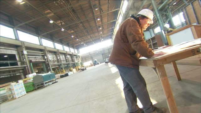 vídeos de stock, filmes e b-roll de a man in a hardhat looks at building plans in a warehouse. - capacete de trabalho