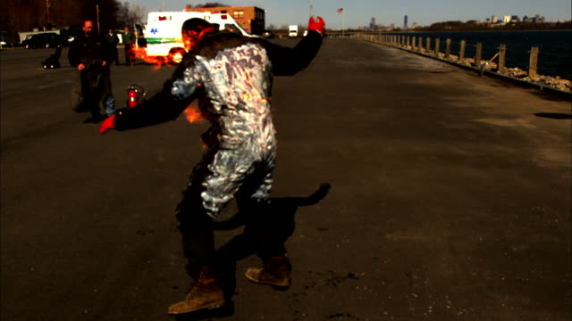 a man in a jumpsuit thrashes about as flames cover his back. - stunt person stock videos & royalty-free footage