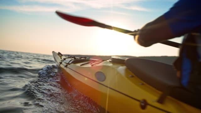 vídeos de stock, filmes e b-roll de slo mo homem num caiaque passando no mar, no sol - kayaking