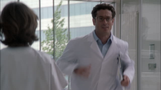 a man in a lab coat runs into a hospital lobby. - coat stock videos & royalty-free footage