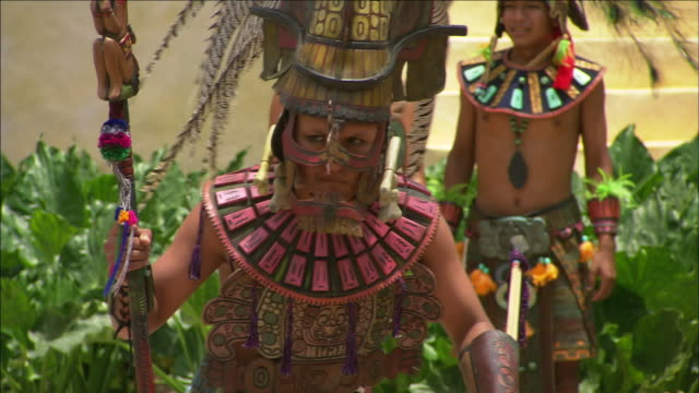 a man in a mayan costume slowly walks in front of bystanders. - weaponry stock videos & royalty-free footage