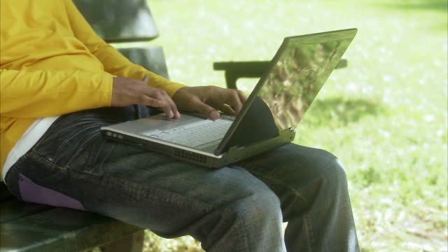 man in a park using a laptop, sweden. - hot desking stock videos & royalty-free footage