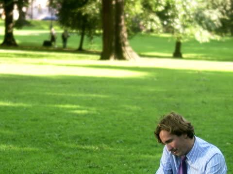 vidéos et rushes de a man in a park using a laptop sweden. - un seul homme d'âge moyen
