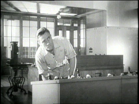 man in a power plant stands behind a control panel turning knobs and adjusting gauges. - 1959年点の映像素材/bロール