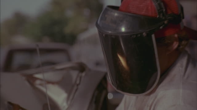 A man in a protective visor welds a piece of metal.