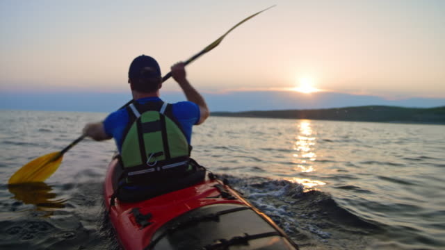 vídeos de stock e filmes b-roll de slo mo man in a red sea kayak passing by on the water at sunset - kayaking