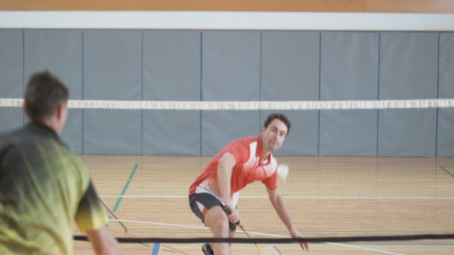 vídeos de stock, filmes e b-roll de homem de camisa vermelha, jogando badminton indoor com seu amigo - badmínton esporte