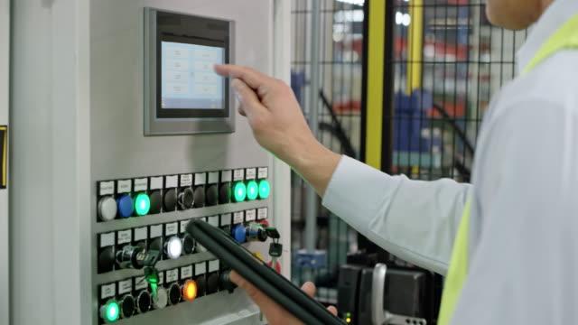 vídeos y material grabado en eventos de stock de hombre en un chaleco de seguridad ingresar datos en la máquina usando la pantalla táctil en la fábrica - manufacturing machinery