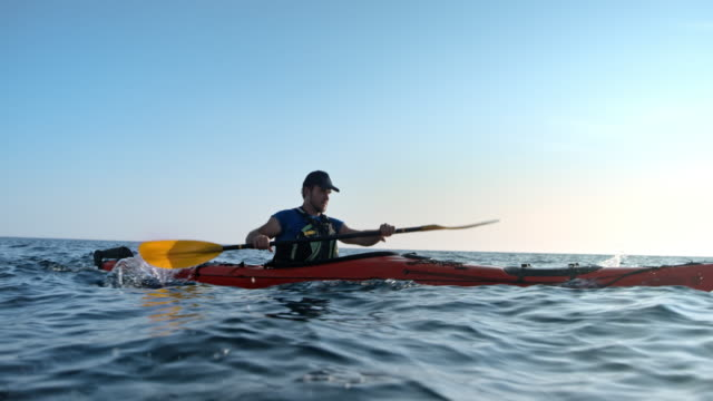 slo mo ts man in a sea kayak paddling in sunshine - pagaiare video stock e b–roll