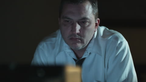 vídeos de stock, filmes e b-roll de man in a shirt and tie watching television in a dark room - assistir tv