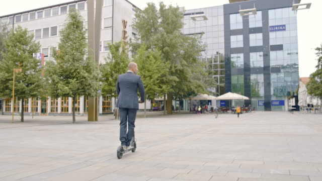 slo mo man in a suit checking his smartphone while riding an electric scooter - alla moda video stock e b–roll