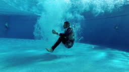 A man in a suit jumps into the pool, tumbles under the water and floats to the surface in a cloud of bubbles. Slow motion. Underwater photography. 4K. 25 fps.