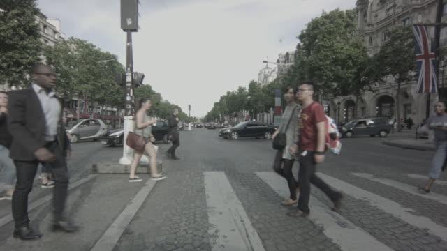 a man in a suit runs across a busy pedestrian crossing on the champs-élysées in paris, france - ヨーロッパ文化点の映像素材/bロール