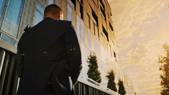 vidéos et rushes de slo mo homme dans un costume marchant le long d'un immeuble de bureaux au coucher du soleil - one man only