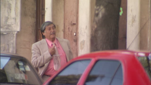 a man in a suit wanders around lost in a run-down neighborhood in mexico city, mexico. - reminder stock videos and b-roll footage