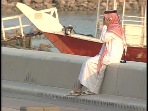 a man in a thawb sits on a dock and talks on his cell phone as women walk by in doha qatar - dish dash stock videos & royalty-free footage