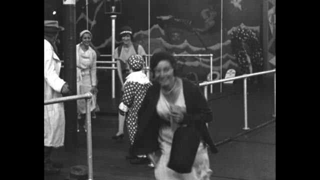 vídeos y material grabado en eventos de stock de a man in a tramp outfit and a dwarf clown look on and push several ladies over a blast of air which raises their skirts at the coney island funhouse... - enano