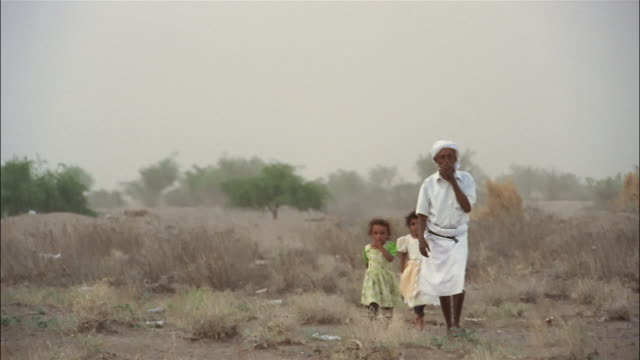 a man in a turban walks with two small girls in the desert. - yemen stock videos and b-roll footage