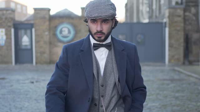 vídeos y material grabado en eventos de stock de un hombre con un traje de tweed caminando hacia la cámara con actitud en una misión - gorra