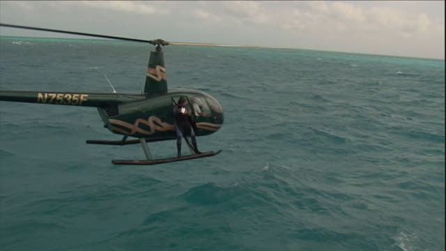 a man in a wetsuit jumps from a helicopter into an ocean. - buoy stock videos & royalty-free footage