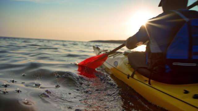 slo mo man in a yellow sea kayak passing by in sunshine - kayaking stock videos & royalty-free footage