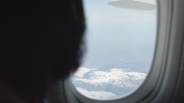 man in an airplane opens the window blind and sees snow on the mountains - business travel stock videos & royalty-free footage