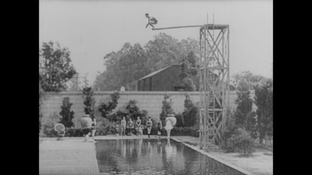 1921 man (buster keaton), in an attempt to impress a woman (virginia fox), dives from a diving board but misses the pool and dives all the way to china - 1921 stock videos & royalty-free footage