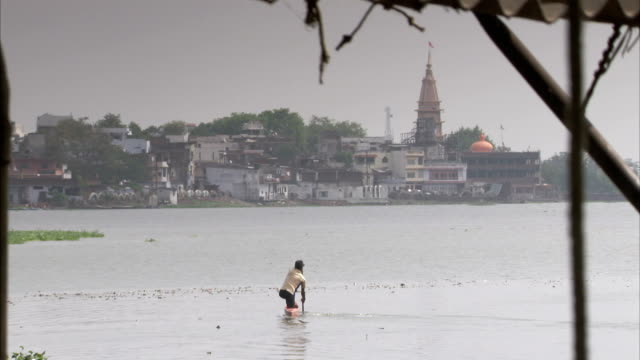 stockvideo's en b-roll-footage met a man in an orange kayak steers his vessel towards the bhopal shoreline. available in hd. - bhopal
