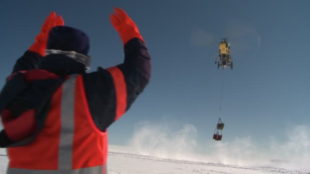 A man in an orange vest and gloves stands in a snowfield and directs a helicopter carrying a giant container. Available in HD.