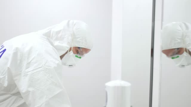 stockvideo's en b-roll-footage met man in anti-contagion clothing doing cleaning tasks. fights the coronavirus. - preventie