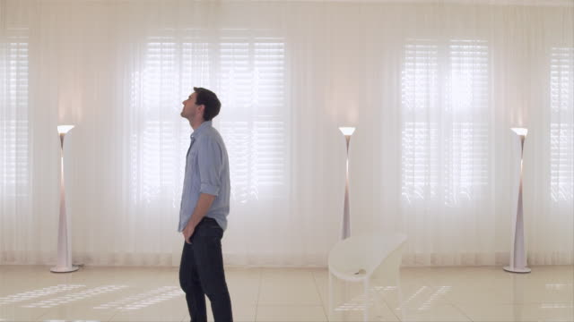 vidéos et rushes de ms ds ws  man in apartment, woman entering frame embracing man  and spinning around - lampe électrique
