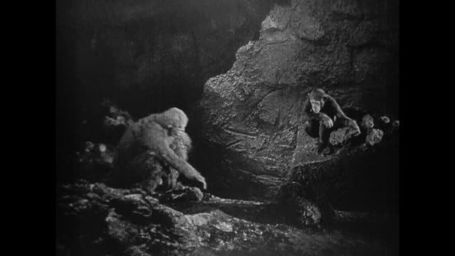 1925 Man in ape suit and real chimpanzee leave cave