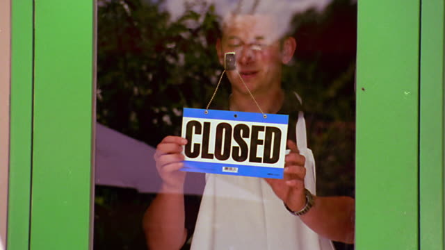 ms man in apron behind glass door turning 'closed' sign to 'open' / reflection in glass - closed sign stock videos & royalty-free footage