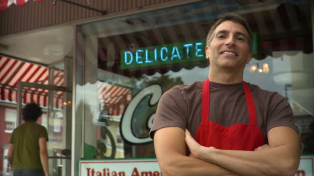 vidéos et rushes de la ms man in apron standing in front of delicatessen and smiling at camera - fierté