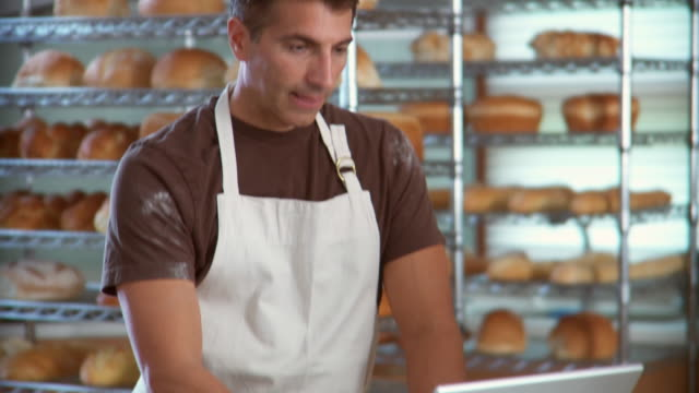 td man in apron working on laptop computer in bakery / racks of bread in background - pane in cassetta video stock e b–roll