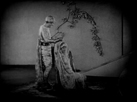 vidéos et rushes de man in arabian costume standing on magic carpet with woman / feature - 1924