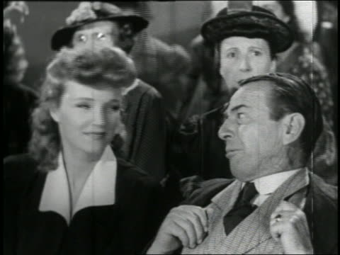 b/w 1941 man in audience with thumbs in vest laughing hysterically / woman sitting by him / feature - audience stock videos & royalty-free footage