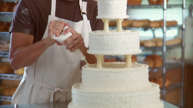 tu man in bakery decorating wedding cake and smiling at camera / racks of bread in background - renovierung themengebiet stock-videos und b-roll-filmmaterial