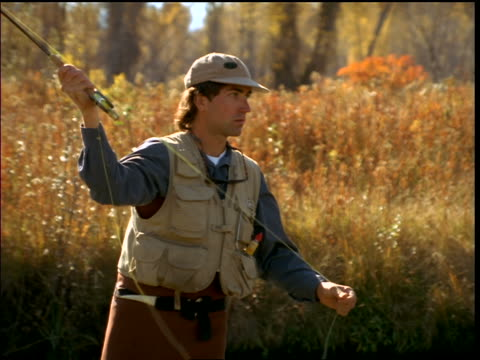 man in baseball cap fly fishing / zoom in to close up of hands - baseball cap stock videos & royalty-free footage