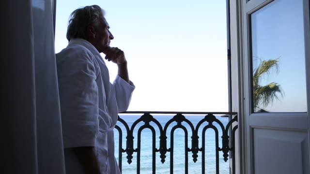 man in bathrobe pauses at veranda doors, looks out to sea - only mature men stock videos & royalty-free footage
