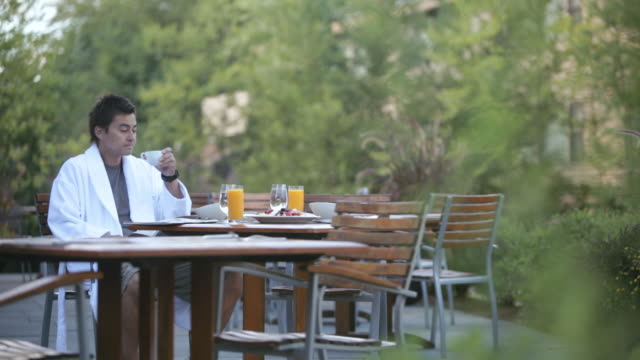ds man in bathrobe sipping coffee and reading paper at outdoor breakfast table / stowe, vermont, united states - vermont stock-videos und b-roll-filmmaterial