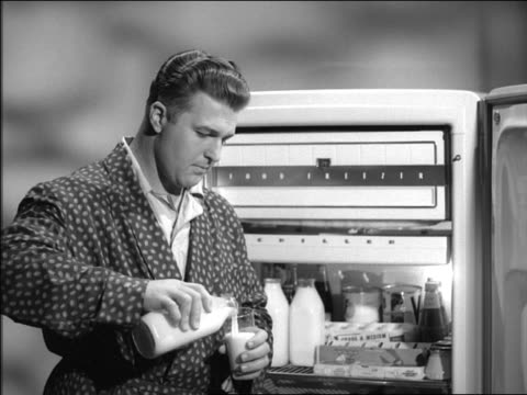 b/w 1954 man in bathrobe standing in front of open refrigerator pouring + drinking milk - 1954 stock videos & royalty-free footage