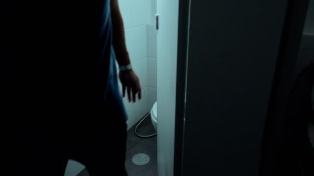 4 k: 浴室の男はドアを開けてゆっくりと夜に - お手洗い点の映像素材/bロール
