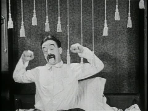 b/w 1923 man (snub pollard) in bed stretching / short - 1923 stock videos & royalty-free footage