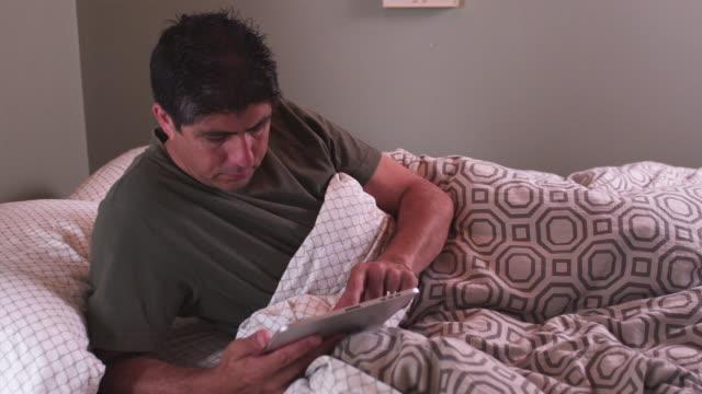 vídeos y material grabado en eventos de stock de ms man in bed under covers using an digital tablet / portland, oregon, united states - manta ropa de cama