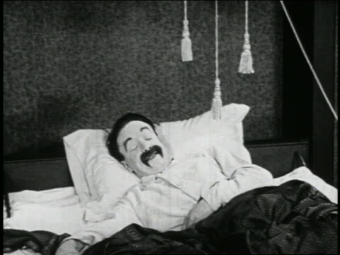 b/w 1923 man (snub pollard) in bed waking up + pulling ropes hanging above him / newsreel - 1923 stock videos & royalty-free footage