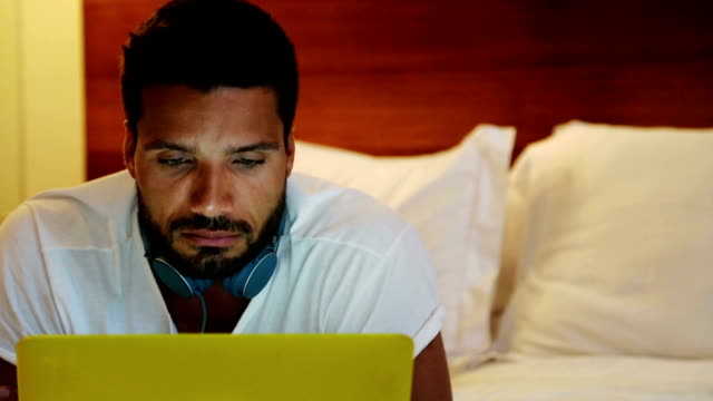 man in bed with yellow laptop - vorderansicht stock-videos und b-roll-filmmaterial
